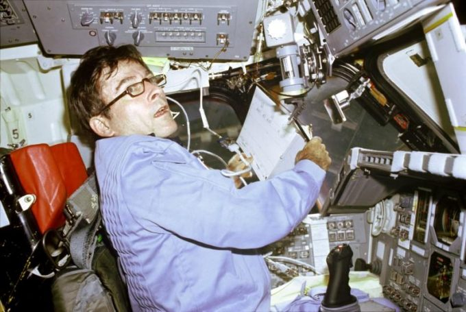 FILE PHOTO: John W. Young, STS-1 mission Commander, prepares to log flight-pertinent data in a loose-leaf flight activities notebook onboard the Space Shuttle Columbia April 14, 1981. Young is seated in the commander's station on the port side of Columbia's forward flight deck. NASA/Kennedy Space Center/Handout via REUTERS/File Photo