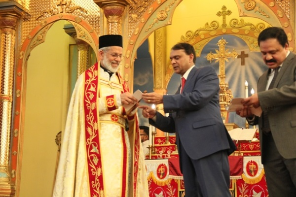 Dr Philip George giving Banquet ticket to Rev Fr M K Kuriakose