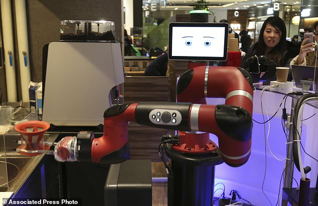 "Robot barista named ""Sawyer"" makes a coffee at Henn-na Cafe, Japanese meaning ""Strange Cafe""in Tokyo, Friday, Feb. 2, 2018. The cafe's robot barista brews and serves coffee as the rapidly aging country seeks to adapt to shrinking workforce. The arm robot ""Sawyer"" debuted this week in Tokyo's downtown business and shopping district of Shibuya. (AP Photo/Koji Sasahara)"