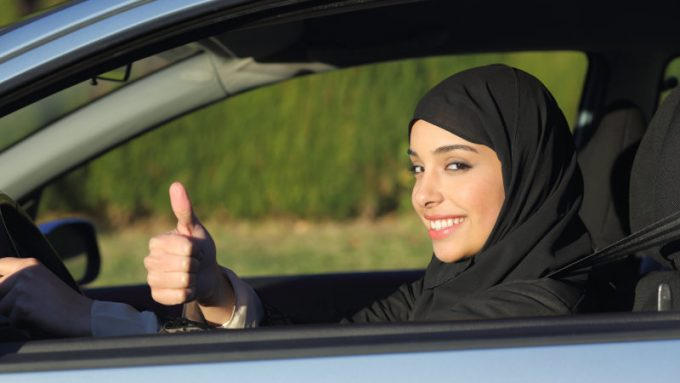 Happy arab saudi woman driving a car with thumb up smiling with a headscarf