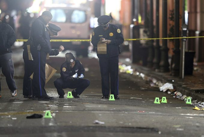 A crime scene technician collects a shell casing as New Orleans Police investigate a fatal shooting at Iberville and Bourbon streets early Sunday, Nov. 27, 2016, in New Orleans. (Michael DeMocker/NOLA.com The Times-Picayune via AP)