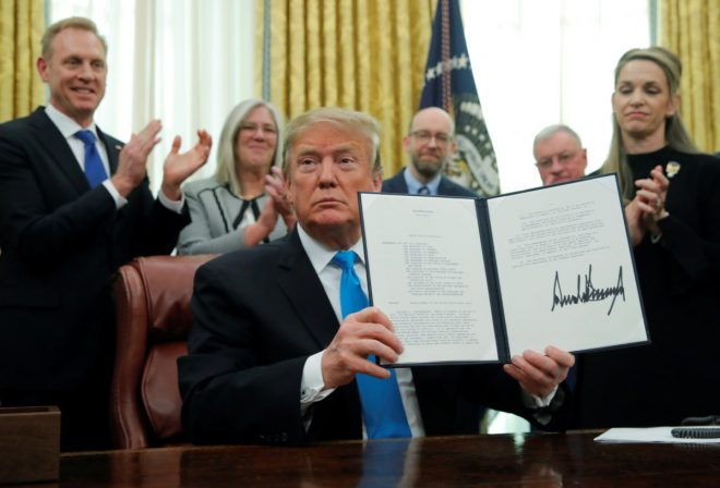 "U.S. President Donald Trump displaus the ""Space Policy Directive 4"" after signing the directive  establish a Space Force as the sixth branch of the Armed Forces in the Oval Office at the White House in Washington, U.S., February 19, 2019. REUTERS/Jim Young"