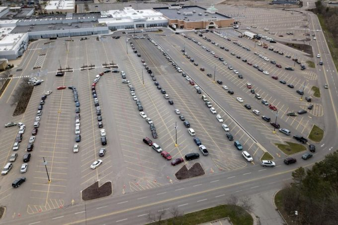 Cars line up in the parking lot of a drive thru food pantry at a mall in Grand Rapids