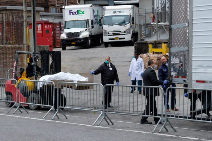 Workers place bodies of coronavirus victims in a cold storage truck outside Brooklyn Hospital Center