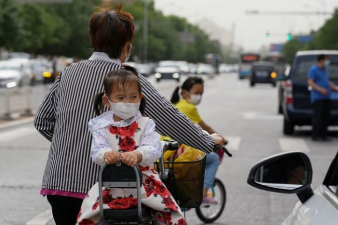 BEIJING, CHINA - MAY 11: A young girl wearing face masks sitting on a bicycle on May 11, 2020 in Beijing, China. Life in Beijing is slowly returning to normal following a city-wide lockdown on January 25 to contain the coronavirus (COVID-19) outbreak. (Photo by Lintao Zhang/Getty Images)
